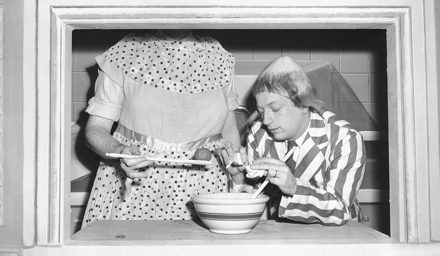 FILE- In this Jan. 2, 1952, file photo, Ray Goulding, left, playing the character called of Mary McGoon, instructs Bob Elliott, playing the character Uncle Eugene, right, on meatball stuffing. Elliott, half of the enduring television and radio comedy team Bob and Ray and father of actor-comedian Chris Elliott, died Tuesday, Feb. 2, 2016, Rick Gagne, director of the Brackett Funeral Home, said Wednesday. He was 92. (AP Photo/WAB, File)