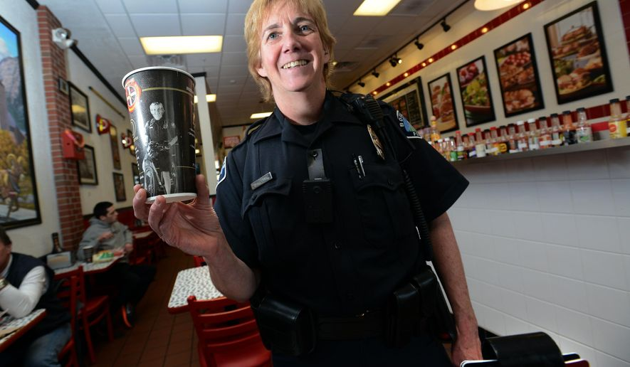 In this photo taken on Jan. 25, 2016, Boulder Officer Jenny Paddock holds a photo of herself on a Hometown Heroes cup at Firehouse Subs in Boulder, Colo. Paddock's image now graces a series of drink cups served around the country to promote the fast-food chain's foundation that helps buy equipment for law enforcement and emergency personnel. (Paul Aiken/Daily Camera via AP) NO SALES; MANDATORY CREDIT