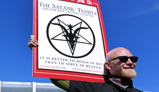 In this Jan. 24, 2015 photo, Chris Bridges holds a sign for the Satanic Temple during a protest outside of an all-day prayer rally headlined by Louisiana Gov. Bobby Jindal in Baton Rouge. (AP Photo/Jonathan Bachman, File)
