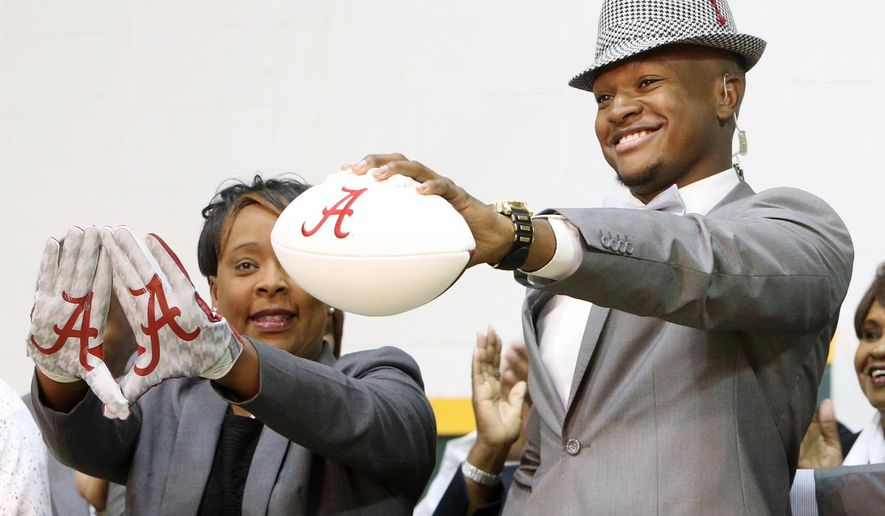 Gordo High School football player Ben Davis, with his mother Faye, left, holds up a football after committing to attend Alabama during a national signing day Program at Gordo High School, Wednesday, Feb. 3, 2016, in Tuscaloosa Ala. (Michelle Lepianka Carter/The Tuscaloosa News via AP) NO SALES; MANDATORY CREDIT