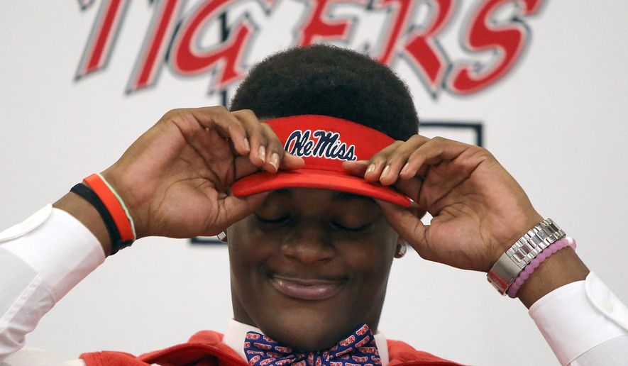 Football player Tariqious Tisdale puts on an Ole Miss visor after he signed his letter of intent to attend Mississippi  during national signing day at Lexington High School, Wednesday, Feb. 3, 2016, in Lexington, Tenn. (C.B. Schmelter/The Jackson Sun via AP) NO SALES; MANDATORY CREDIT