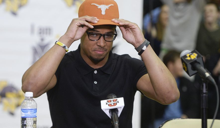 Nacogdoches High School football player Brandon Jones dons a UT cap as he announces that he will be attending the University of Texas to play NCAA college football, Wednesday, Feb. 3, 2016, during a national signing day event in Nacogdoches, Texas, (Victor Texcucano/The Daily Sentinel via AP) MANDATORY CREDIT