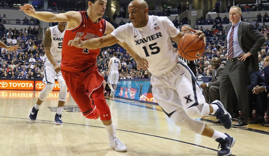 Xavier guard Myles Davis (15) drives to the basket in front of St. John's guard Federico Mussini (4) during the first half of an NCAA college basketball game Wednesday, Feb. 3, 2016, in Cincinnati. (AP Photo/Gary Landers)
