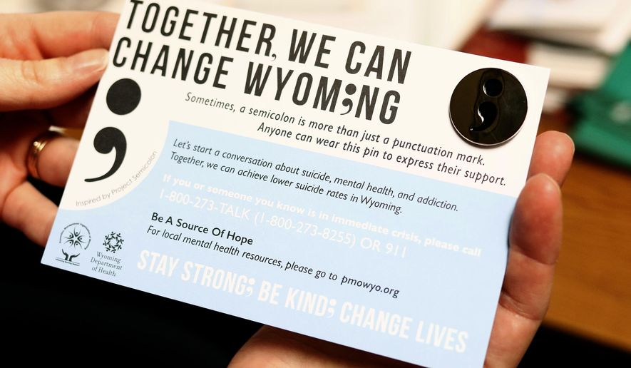 Spring Wilkins, community prevention professional with the Prevention Management Organization of Wyoming, shows a a card carrying a semicolon button at the organization's Gillette, Wyo., office. (Ed Glazar/Gillette News Record via AP) TV OUT; MANDATORY CREDIT