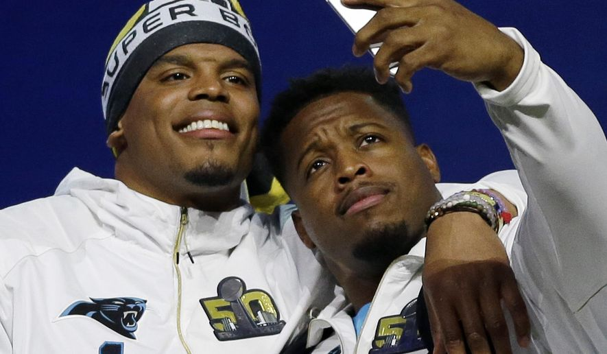 FILE - In this Monday, Feb. 1 2016, file photo, Carolina Panthers' Jonathan Stewart takes a selfie with Cam Newton during Opening Night for the NFL Super Bowl 50 football game in San Jose, Calif. Whether it is Newton photobombing his teammates getting off  the plane at the Super Bowl, Mike Tolbert playing deejay in the team's locker room or teammates attending Star Wars movies together, the Panthers have, and continue to be, a loose, tight-knit bunch entering Super Bowl week. (AP Photo/David J. Phillip, File)