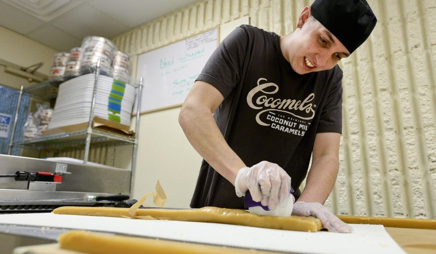 In this photo taken on Friday, Jan. 22, 2016,  Head Cook, Research and Development technician and Plant Manager Luis Bustillos cuts coconut milk caramels before packaging at their production facility in Longmont, Colo., The makers of Boulder County's Cocomels got an award from a San Francisco nonprofit group for their emphasis on sustainability in products and practices.  (Matthew Jonas /The Daily Times Call via AP) NO SALES; MANDATORY CREDIT