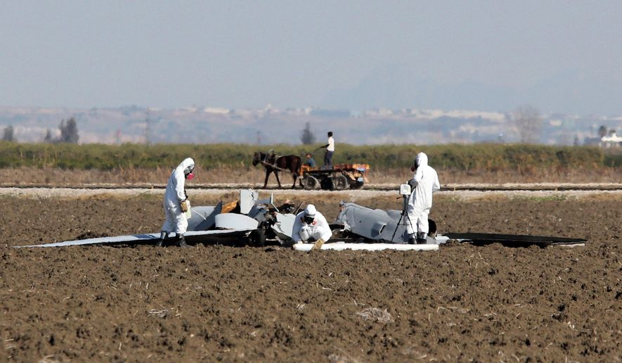 U.S. military forensic experts investigate the remains of a Predator drone aircraft near Incirlik Air Base, Adana, Turkey, Wednesday, Feb. 3, 2016.  U.S. military officials have confirmed Turkish media reports that an American Predator drone has crashed on a field near Incirlik Air Base in southern Turkey. U.S. Air Forces Europe spokeswoman Capt. Lauren Ott said the remotely piloted aircraft crashed early on Wednesday. No one was hurt in the incident.(AP Photo)