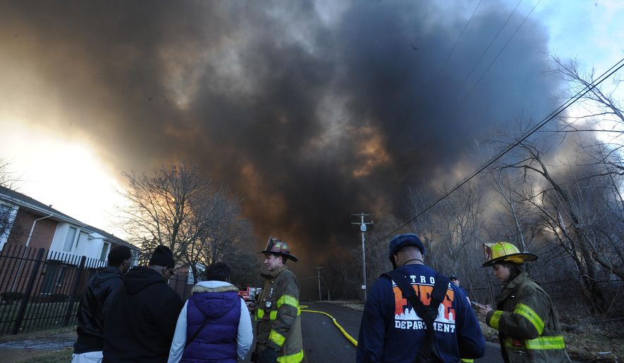 Firefighters speak with area residents as black smoke nearly blots out the sky from a warehouse in Highland Park, Mich., on Wednesday, Feb. 3, 2016.  No injuries are reported from the fire, which was reported early Wednesday. Crews from multiple departments responded.  (Brandy Baker/Detroit News via AP)  DETROIT FREE PRESS OUT; HUFFINGTON POST OUT; MANDATORY CREDIT