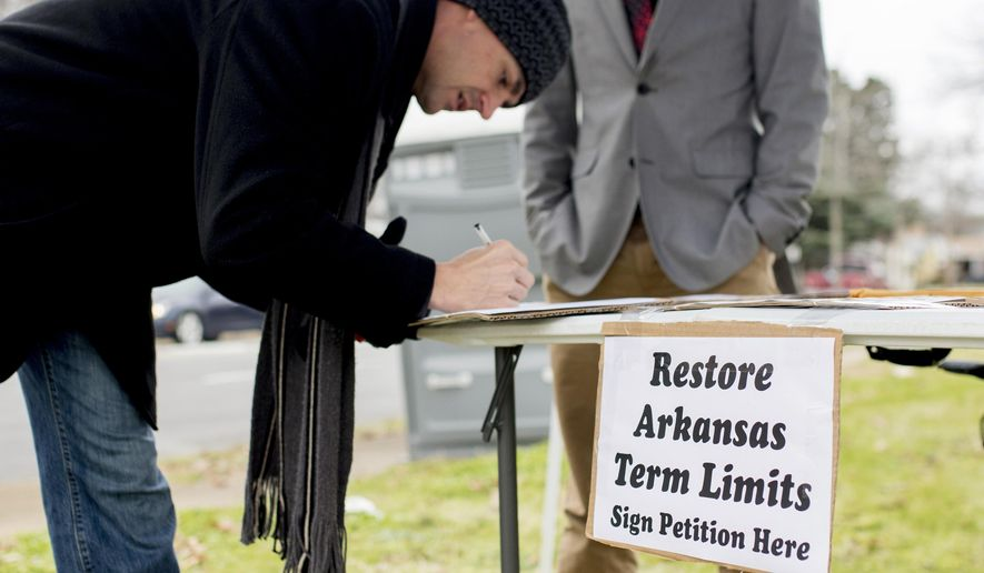In this Jan. 18, 2016 photo, Stuart Rubio, left, signs a petition to limit lawmakers terms before the Martin Luther King Jr. Day parade in Little Rock, Ark. More than two decades after Arkansas became one of the first states to limit how long lawmakers could serve in the Legislature, Republicans who once championed the issue are conflicted. GOP leaders now say they believe lawmakers should be able to stay longer than originally planned. (AP Photo/Gareth Patterson)