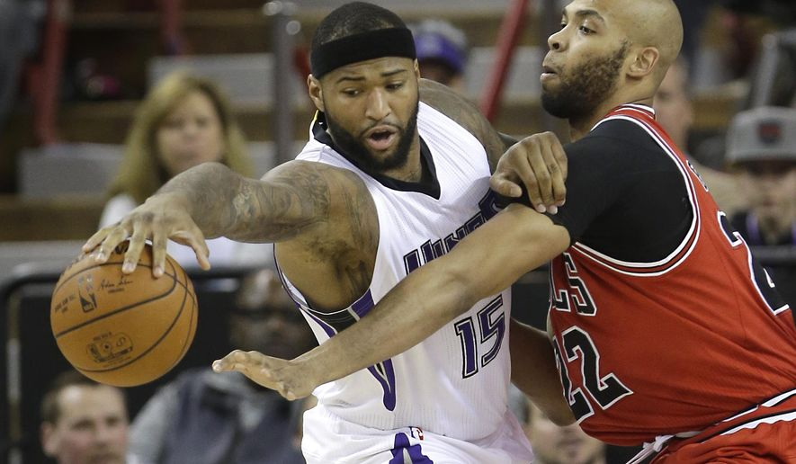 Sacramento Kings center DeMarcus Cousins, left, reaches for the ball against the defensive pressure from Chicago Bulls forward Taj Gibson during the first quarter of an NBA basketball game in Wednesday, Feb. 3, 2016, in Sacramento, Calif.(AP Photo/Rich Pedroncelli)