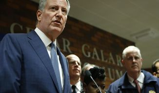 New York City Mayor Bill de Blasio, center, speaks at Lincoln Hospital, Thursday, Feb. 4, 2016, in the Bronx borough of New York after two police officers were shot in a public housing project in the Bronx by an armed suspect who apparently turned the weapon on himself not far from where Mayor Bill de Blasio was delivering his state of the city address Thursday evening. New York City Police Department Chief of Detectives Robert Boyce, listens, right.  (AP Photo/Kathy Willens)