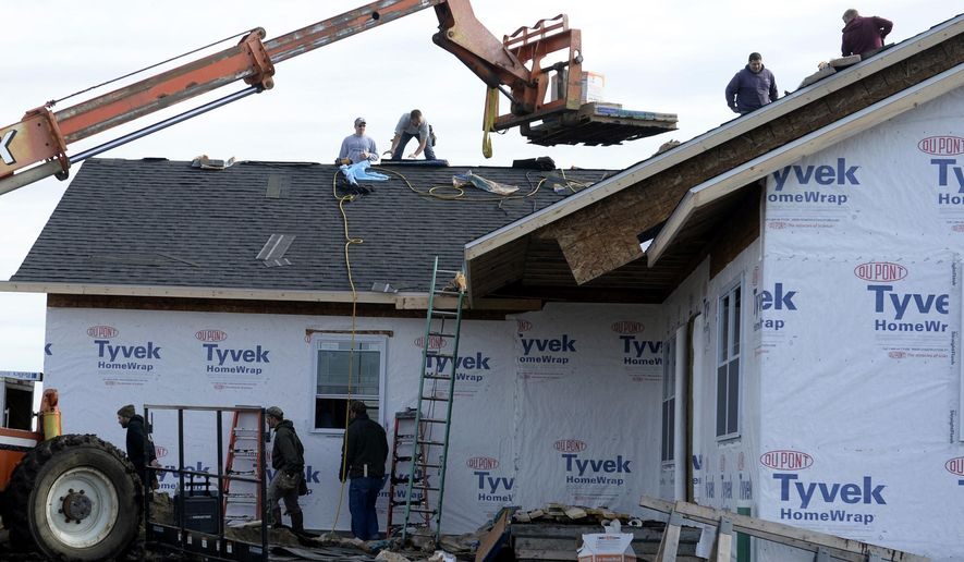 In this photo taken on Saturday, Jan. 30, 2016, volunteers work to help contractor Kurt Schulte finish a house in Mediapolis, Iowa. Schulte and Darin Bush, who died in a vehicle accident, were business partners, and the home was Bush's last project. (Jeff Brown /The Hawk Eye via AP) MANDATORY CREDIT