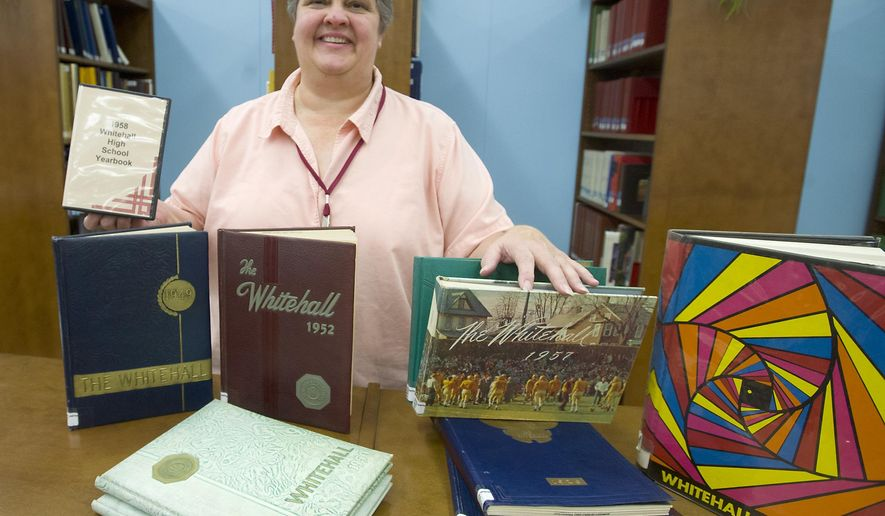 ADVANCE FOR THE WEEKEND OF FEB. 6 - In this Tuesday, Jan. 12, 2016 photo, Library Director Patty Vehey holds a digitized copy of the 1958 Whitehall High School Yearbook, next to others being digitized, at the Whitehall Township Library, Pa. Growing number of libraries making decades worth of high school yearbook collections available online in digital form.  (Harry Fisher/The Morning Call via AP) MANDATORY CREDIT