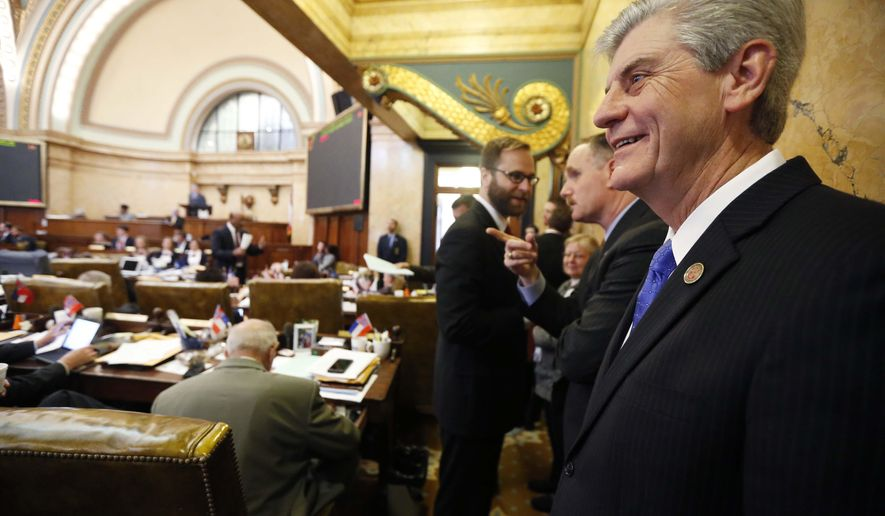 Republican Gov. Phil Bryant, smiles as he listens to the House discussion of an incentive bill for a tire plant in western Hinds County and a shipyard in Gulfport, Thursday, Feb. 4, 2016, at the Capitol in Jackson, Miss. Bryant set Thursday's special session for the two economic development projects that could create 3,500 jobs. The bill passed the House and was sent to the Senate for consideration. (AP Photo/Rogelio V. Solis)