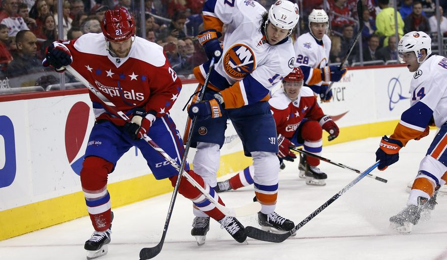 Washington Capitals center Brooks Laich (21) and New York Islanders left wing Matt Martin (17) go for the puck in the second period of an NHL hockey game, Thursday, Feb. 4, 2016, in Washington. (AP Photo/Alex Brandon)