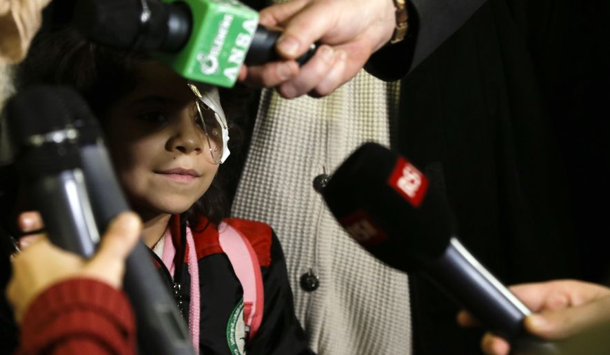 "Falak al Hourani, 7-year-old, suffering from a rare form of eye cancer, stands beside her mother Yasmina Al Hourani, as they are interviewed by journalists upon their arrival lat Rome's Fiumicino international airport, Thursday, Feb. 4, 2016. Little Falak al Hourani, her parents and 6-year-old brother Hussein landed on a commercial flight at Rome's Leonardo Da Vinci airport thanks to the ""humanitarian corridor"" project launched by the Rome-based Catholic Sant'Egidio Community and the Federation of Protestant Churches in Italy. The two groups lobbied the Italian government to grant 1,000 humanitarian visas for particularly vulnerable refugees in camps in Lebanon, Morocco and Ethiopia. (AP Photo/Gregorio Borgia)"