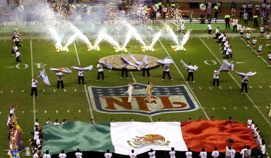 FILE - In this Oct. 2, 2005 file photo, performers unfurl a Mexican national flag prior to the start of the regular season NFL game between the Arizona Cardinals and San Francisco 49ers at Azteca Stadium in Mexico City. The NFL is planning to play a 2016 regular-season game in Mexico City, a person familiar with the decision tells The Associated Press. The person spoke on condition of anonymity because the NFL has not officially announced the Oakland Houston football matchup.  (AP Photo/Marco Ugarte)