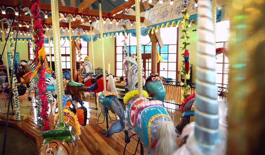 The newly refurbished Silver Beach Carousel reopens after being closed for a month for renovations, in St. Joseph, Mich., Thursday, Feb. 4, 2016. The carousel is arranged in three rings of 48 figures, ranging from white horses that are replicas of the original Silver Beach carousel, an attraction from the early part of the 20th century, to zebras, otters and flamingos. (Chelsea Purgahn /Kalamazoo Gazette-MLive Media Group via AP) LOCAL TELEVISION OUT; LOCAL RADIO OUT; MANDATORY CREDIT
