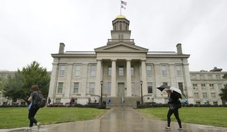 In this Oct. 2, 2014 file photo, students walk across campus at the University of Iowa in Iowa City, Iowa. (AP Photo/Charlie Neibergall, File)