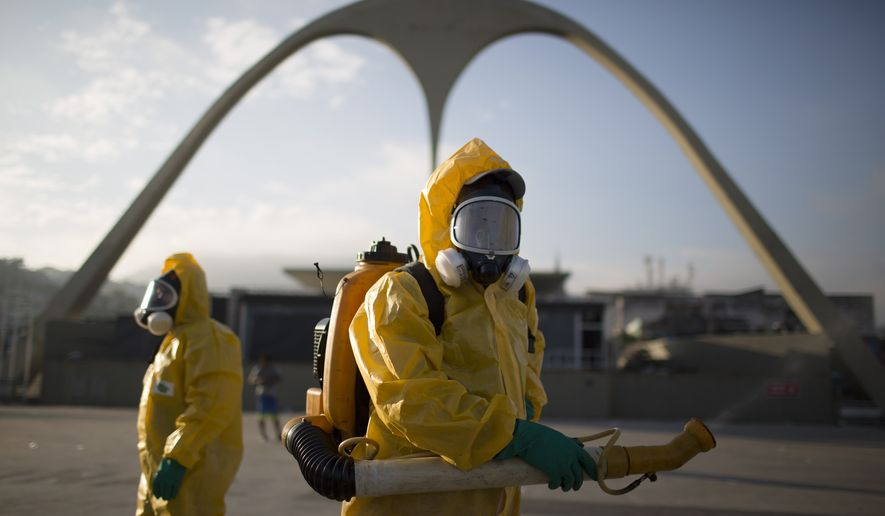 In this Tuesday, Jan. 26, 2016, file photo, health workers stands in the Sambadrome spraying insecticide to combat the Aedes aegypti mosquito that transmits the Zika virus in Rio de Janeiro, Brazil. (AP Photo/Leo Correa, File)