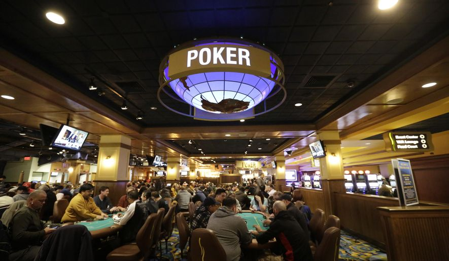 In this Wednesday, Feb. 3, 2016 photo patrons play poker in a designated area at Twin River Casino, in Lincoln, R.I. Casinos far from Las Vegas are experimenting with different ways to draw millennials. Twin River Casino removed 274 slot machines to make way in December for more poker and other table games favored by younger gamblers. (AP Photo/Steven Senne)