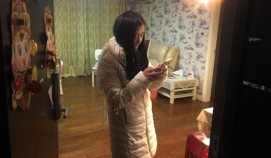 In this Feb. 2, 2016 photo, Chen Xiao, a real estate agent, checks on her smartphone as she prepares to leave her house to go back to her hometown for the upcoming Chinese Lunar New Year, in Shanghai, China. The hundreds of millions of Chinese heading home for Lunar New Year have a relatively new travel option this year: mobile apps to find carpool partners to share costs in what is a novel concept for most Chinese. The apps give an alternative to pricey airfares and hard-to-score train tickets. (AP Photo/Paul Traynor)