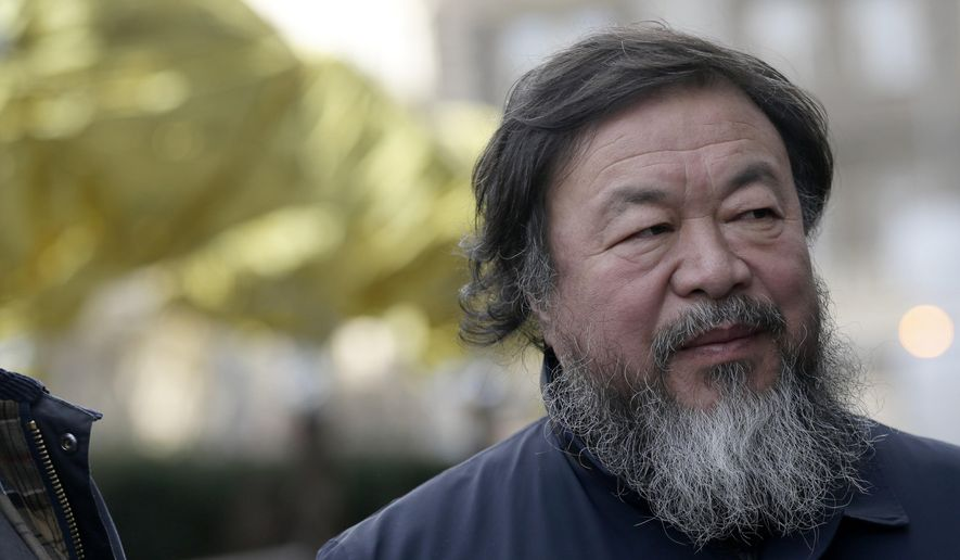 Chinese activist and artist Ai Weiwei poses for a photograph standing next to his 12 sculptures installation called Zodiac placed in front of the National Gallery in Prague, Czech Republic, Friday, Feb. 5, 2016. Ai Weiwei has wrapped with thermal blankets his bronze animal heads meant to recreate the traditional Chinese zodiac to protest the situation of the migrants coming to Europe. (AP Photo/Petr David Josek)