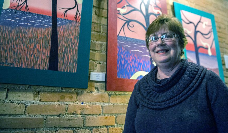 In this Jan. 21, 2016 photo, Sue Trowbridge stands next to her paintings on exhibit at Brownstone Coffeehouse in Battle Creek, Mich. Trowbridge is a pastor and a painter. She knows about heaven's calls and natural gifts. She's even seen heaven and nature sing. What she didn't understand was how to be both. (Al Lassen/Battle Creek Enquirer via AP)