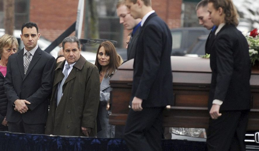 In this Dec. 30, 2015 photo, Richard Dabate, left, watches the casket bearing his late wife Connie Dabate being carried during her funeral outside St. Bernard Roman Catholic Church in Vernon, Conn. While responding to a burglary alarm on Dec. 23, authorities found Connie Dabate, mother of two children, shot to death and her husband Richard Dabate injured inside their Ellington, Conn., home. No arrests have been made, leaving local residents concerned and speculating.  (Jim Michaud/Journal Inquirer via AP)   MANDATORY CREDIT