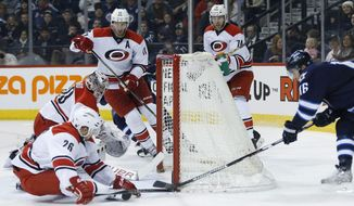 Carolina Hurricanes goaltender Cam Ward (30) watches as teammate John-Michael Liles (26) stops the wraparound attempt by Winnipeg Jets' Andrew Ladd (16) as Hurricanes' Jordan Staal (11) and Jaccob Slavin (74) defend during the second period of an NHL hockey game Friday, Feb. 5, 2016, in Winnipeg, Manitoba. (John Woods/The Canadian Press via AP)