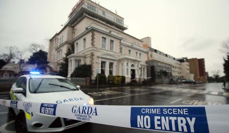 A police (Garda) cordon outside the Regency Hotel in Dublin, Ireland, after one man died and two others were injured following a shooting incident at the hotel, Friday Feb. 5, 2016.  According to witness reports, two gunmen believed to be armed with assault rifles and disguised as police opened fire Friday on boxing fans during a boxing tournament weigh-in at the Dublin hotel, killing one man and wounding two others. (Niall Carson / PA via AP) UNITED KINGDOM OUT - NO SALES - NO ARCHIVES