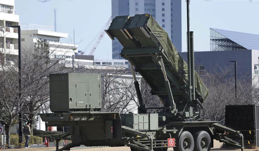 In this Sunday, Jan. 31, 2016, file photo, a man walks past a PAC-3 Patriot missile unit deployed for North Korea's rocket launch at the Defense Ministry in Tokyo. Japan has deployed PAC-3 missile batteries in the heart of Tokyo to defend its airspace from incoming rocket debris. South Korea is reportedly mobilizing two Aegis-equipped destroyers. (AP Photo/Shizuo Kambayashi, File)