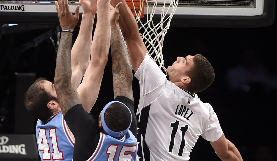 Brooklyn Nets center Brook Lopez (11) takes aim for the basket past Sacramento Kings center Kosta Koufos (41) and center DeMarcus Cousins (15) during the first half of an NBA basketball game Friday, Feb. 5, 2016, in New York. (AP Photo/Kathy Kmonicek)