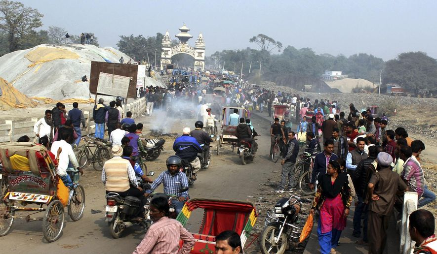 Local residents of Nepal and India living near the border cross a bridge at Birgunj, Nepal, Friday, Feb. 5, 2016. Vehicles have passed through the main border point between the two nations after local residents forcibly removed barriers set up by ethnic protesters who for months have been demanding changes in the new constitution. (AP Photo/Jiyalal Sah)