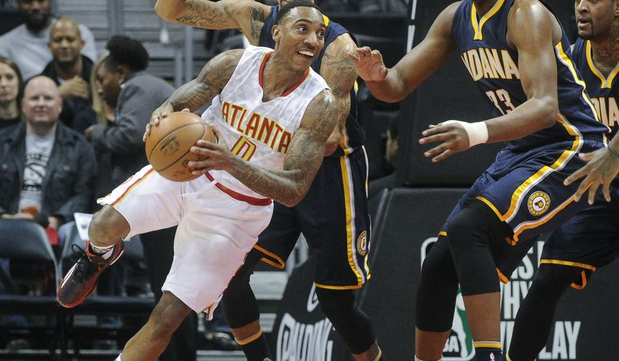Atlanta Hawks guard Jeff Teague, left, looks to pass while losing his footing as Indiana Pacers guard George Hill, and forward Myles Turner, right, defend during the first half of an NBA basketball game, Friday Feb. 5, 2016, in Atlanta. (AP Photo/John Amis)