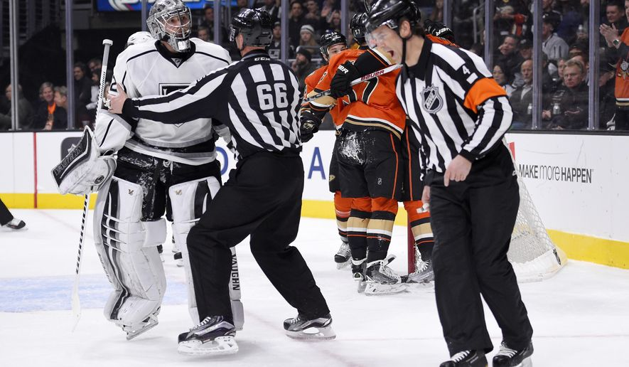 FILE - In this Feb. 4, 2016 file photo, Los Angeles Kings goalie Jonathan Quick, left, is held back away from referee Wes McCauley, right, by linesman Darren Gibbs after Anaheim Ducks left wing David Perron scored on Quick during the first period of an NHL hockey game, in Los Angeles. (AP Photo/Mark J. Terrill, File)