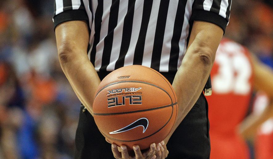 FILE - In this Jan. 3, 2016, file photo, an official holds the ball behind his back during a break in the second half of an NCAA college basketball game between New Mexico and Boise State in Boise, Idaho. Referees undergo nearly as much scrutiny as the teams that want to join in March Madness, with a field of nearly 1,000 that is winnowed to 100 for tournament time. And just like the teams, the refs have to be on their game to keep advancing. (AP Photo/Otto Kitsinger, File)