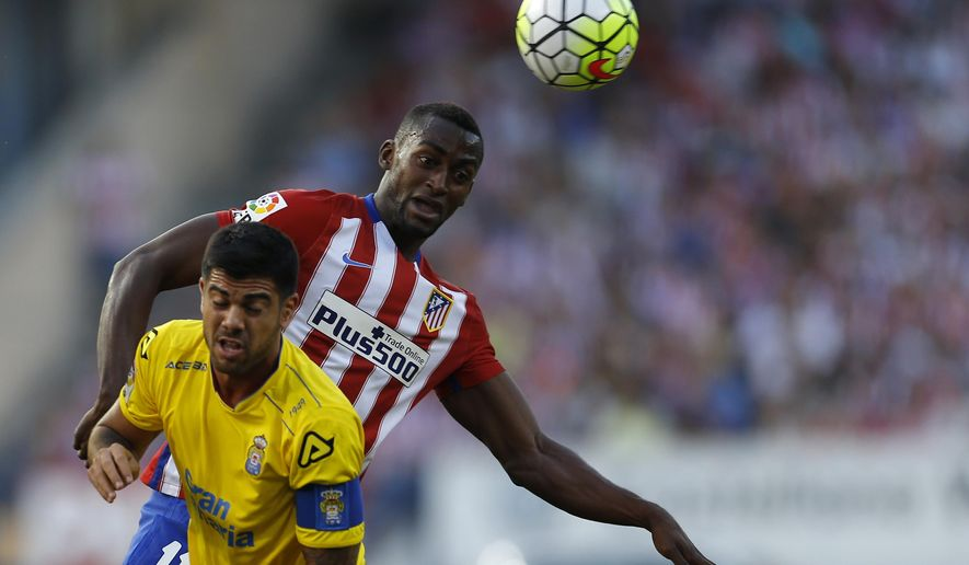 FILE - In this Aug. 22, 2015, file photo, Atletico Madrid's Jackson Martinez, top, goes for a header with Las Palmas' Aythami Artiles during the Spanish La Liga soccer match between Atletico Madrid and Las Palmas at the Vicente Calderon stadium in Madrid, Spain. Guangzhou Evergrande of the Chinese Super League said Wednesday, Feb. 3, 2016, that it has signed Martinez for what is believed to be a new record sum in the Asian transfer market. (AP Photo/Francisco Seco, File)