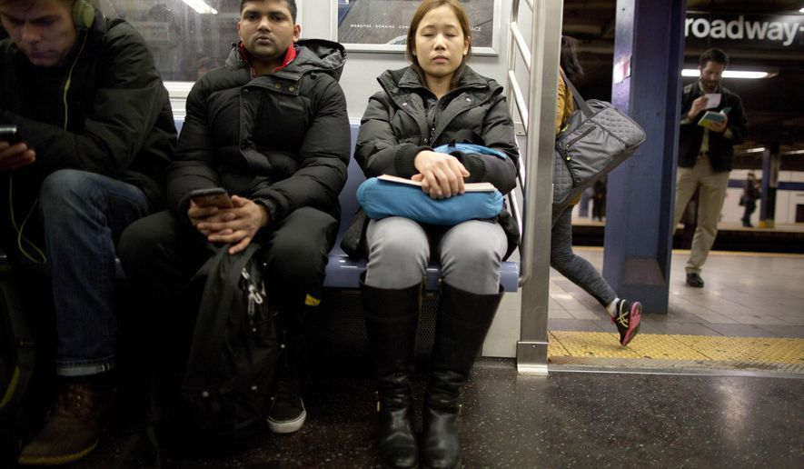 A rush hour commuter shuts her eyes while riding the F train in Manhattan, Thursday, Feb. 4, 2016. About half of all crimes committed in New York City's subway system involve victims who have fallen asleep, a fact that prompted the city's police commissioner to say this week that officers who patrol the system should be waking slumbering passengers for their own good. (AP Photo/Mary Altaffer)
