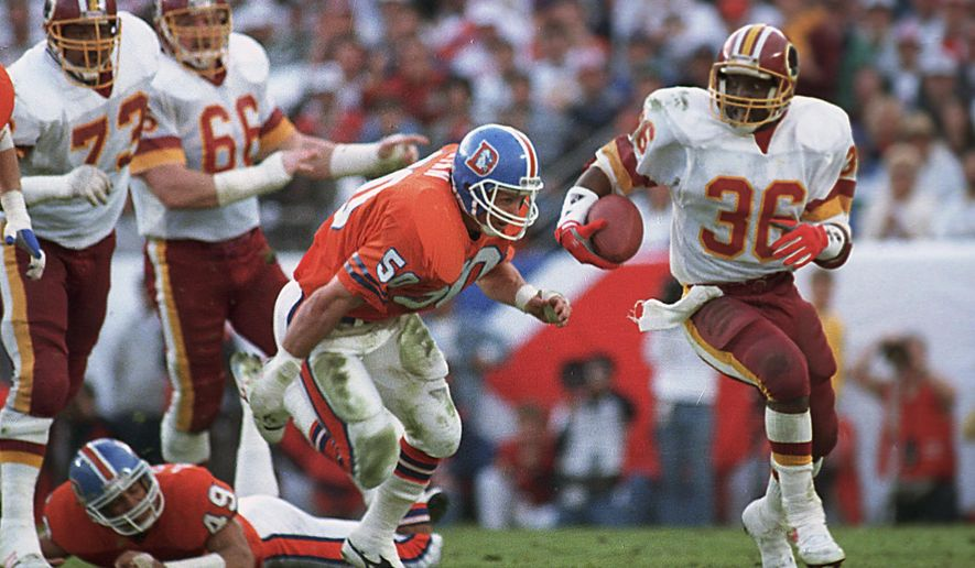 FILE - In this Jan. 31, 1988, file photo, Washington Redskins running back Timmy Smith (36) goes around Denver Broncos linebacker Jim Ryan (50) on a long run during NFL football's Super Bowl XXII in San Diego. Smith finished the game with a Super Bowl-record 204 yards and two scores in a 42-10 win over Denver. Instead of that being a launch to a successful career, drug problems and injuries limited Smith to 15 games and 476 yards rushing for the rest of his career. (AP Photo/Bob Galbraith, File)