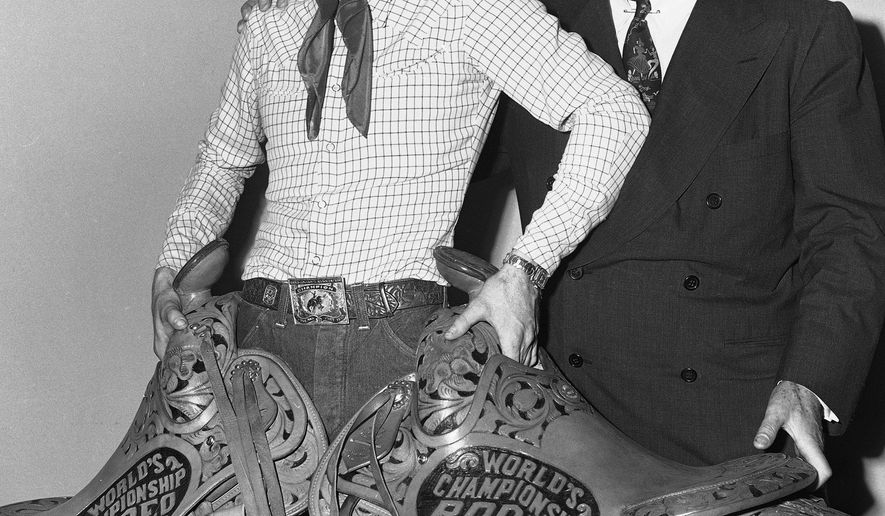 FILE - In this Oct. 21, 1951 file photo, rodeo legend Casey Tibbs, of Fort Pierre, S.D., poses with saddles in New York's Madison Square Garden after taking top honors in rodeo events in the World's Championship Rodeo. At right is Gen. John Reed Kilpatrick, president of Madison Square Garden. Denver filmmaker and South Dakota native Justin Koehler, who is producing a documentary about Tibbs, hopes to wrap up the project by the end of February 2016. (AP Photo/John Lent, File)