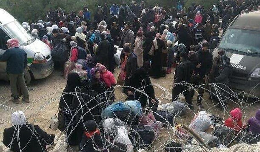 In this image taken Wednesday, Feb. 3, 2016 Syrians wait to enter Turkey at the Bab al-Salam border gate, Syria. Turkish officials say thousands of Syrians have massed on the Syrian side of the border seeking refuge in Turkey. Officials at the government's crisis management agency said Friday Feb. 5, 2016 that it was not clear when Turkey would open the border to allow the group in and start processing them.  (Depo Photos via AP) TURKEY OUT