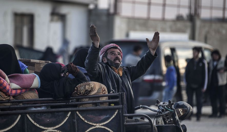 A Syrian man gestures as Syrians gather at the border gate with Turkey, in Bab al-Salam, Syria, Saturday, Feb. 6, 2016. Thousands of Syrians have rushed toward the Turkish border, fleeing fierce Syrian government offensives and intense Russian airstrikes. Turkey has promised humanitarian help for the displaced civilians, including food and shelter, but it did not say whether it would let them cross into the country. (AP Photo/Bunyamin Aygun) TURKEY OUT