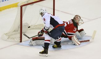 Washington Capitals left wing Alex Ovechkin (8), from Russia, puts the in the net to score a winning goal past New Jersey Devils goalie Cory Schneider (35) during a a shootout in an NHL hockey game Saturday, Feb. 6, 2016, in Newark, N.J. The Capitals won 3-2 in a shootout. (AP Photo/Mel Evans)