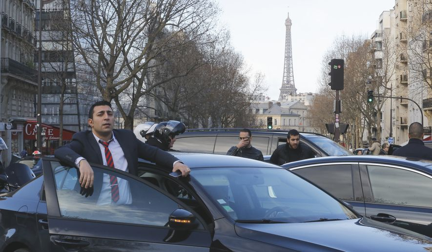 A chauffeur stands by his vehicle during demonstration in Paris, Wednesday, Feb. 3, 2016. Hundreds of French chauffeurs are staging a counter-protest after repeated demonstrations by taxi drivers against looser industry regulations. Tensions have mounted between taxis and chauffeured car services like Uber throughout Europe, with taxis claiming the smartphone-based services are operating outside of the law. (AP Photo/Jacques Brinon)