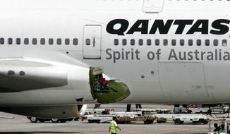 An airline mechanic walks past the damaged right wing fuselage of Qantas Airways Boeing 747-400 passenger plane following an emergency landing at the Ninoy Aquino International Airport in Manila, Philippines, on July 25, 2008. (Associated Press) **FILE**