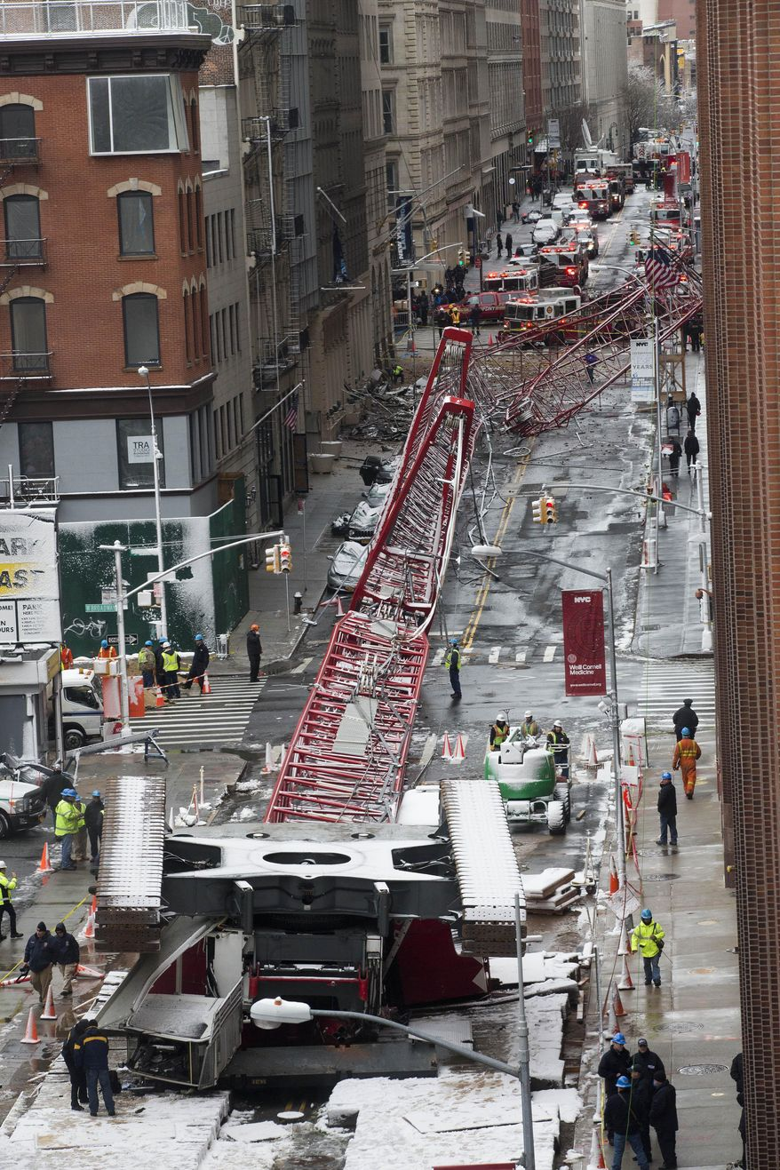 A collapsed crane lies on the street on Friday, Feb. 5, 2016, in New York.  The crane landed across an intersection and stretched much of a block in the Tribeca neighborhood, about 10 blocks north of the World Trade Center. (AP Photo/Mary Altaffer)