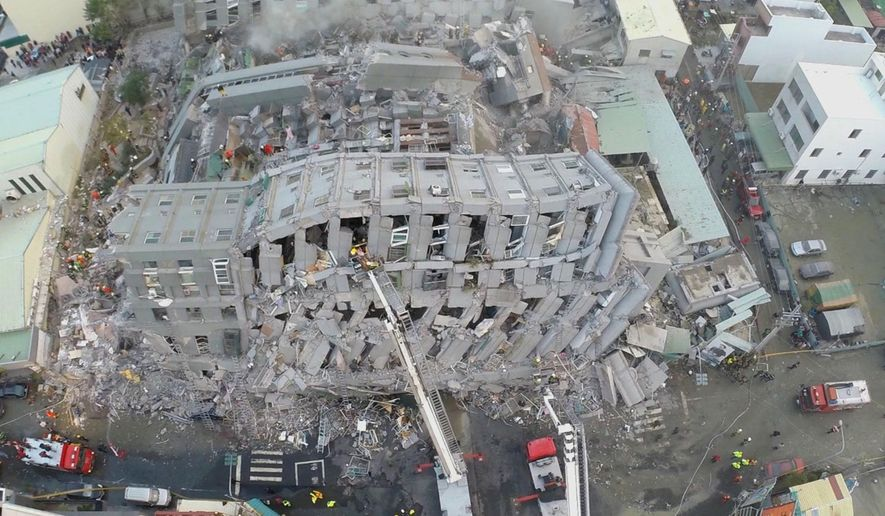 In this photo taken from a drone mounted camera, rescue workers search a collapsed building from an early morning earthquake in Tainan, Taiwan, Saturday, Feb. 6, 2016. A powerful, shallow earthquake struck southern Taiwan before dawn Saturday. (AP Photo) TAIWAN OUT