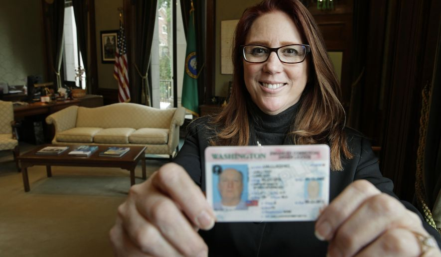 In this photo taken Feb. 1, 2016, Washington Secretary of State Kim Wyman poses for a photo in her office in Olympia, Wash. while holding a sample of a Washington state enhanced drivers license. Months after Washington state saw record low voter turnout, Wyman and several lawmakers say they want to help increase voter engagement with automatic voter registration for some Washingtonians. Senate Bill 6379 and House Bill 2682 would automatically register people who aren't on the voter rolls but already have or apply for an enhanced driver's license or commercial driver's licenses. (AP Photo/Ted S. Warren)