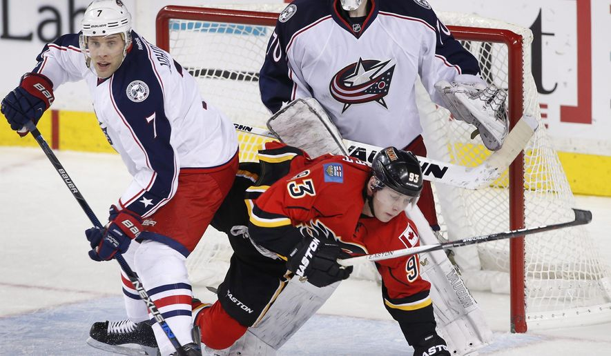 Columbus Blue Jackets' Jack Johnson, left, knocks down Calgary Flames' Sam Bennett in front of Columbus goalie Joonas Korpisalo, from Finland, during the second period of an NHL hockey game, Friday, Feb. 5, 2016 in Calgary, Alberta. (Larry MacDougal/The Canadian Press via AP) MANDATORY CREDIT